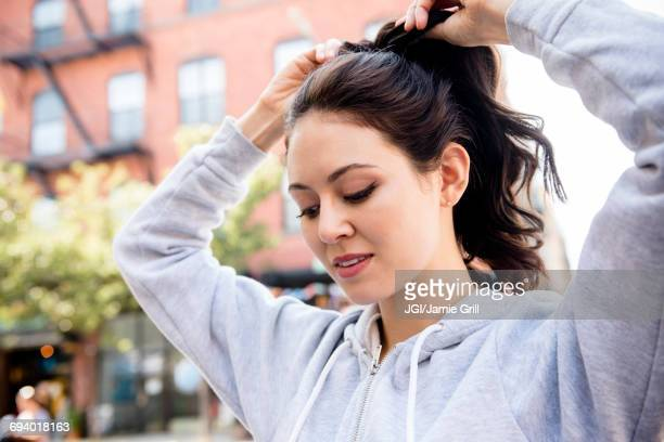 Thai woman tying hair in ponytail