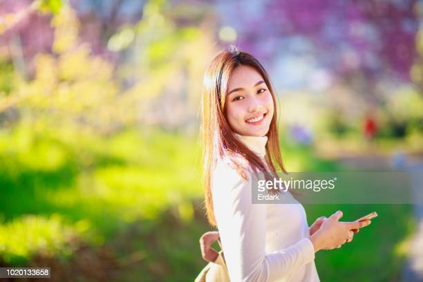 thai woman using phone - cherry blossom in full bloom in tokyo stock pictures, royalty-free photos & images