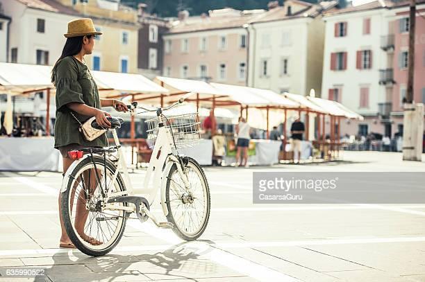 thai woman walking with bicycle on the square of piran - eslovénia imagens e fotografias de stock