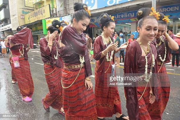 Thai women dressed in traditional costume getting soaked as they walk in a procession during Songkran The Songkran festival which is the traditional...