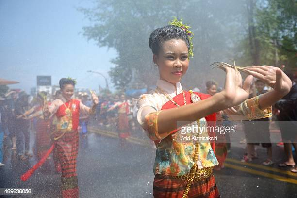 Thai women dressed in traditional costumes perform a traditional dance in a procession during the Songkran festival The Songkran festival is the...