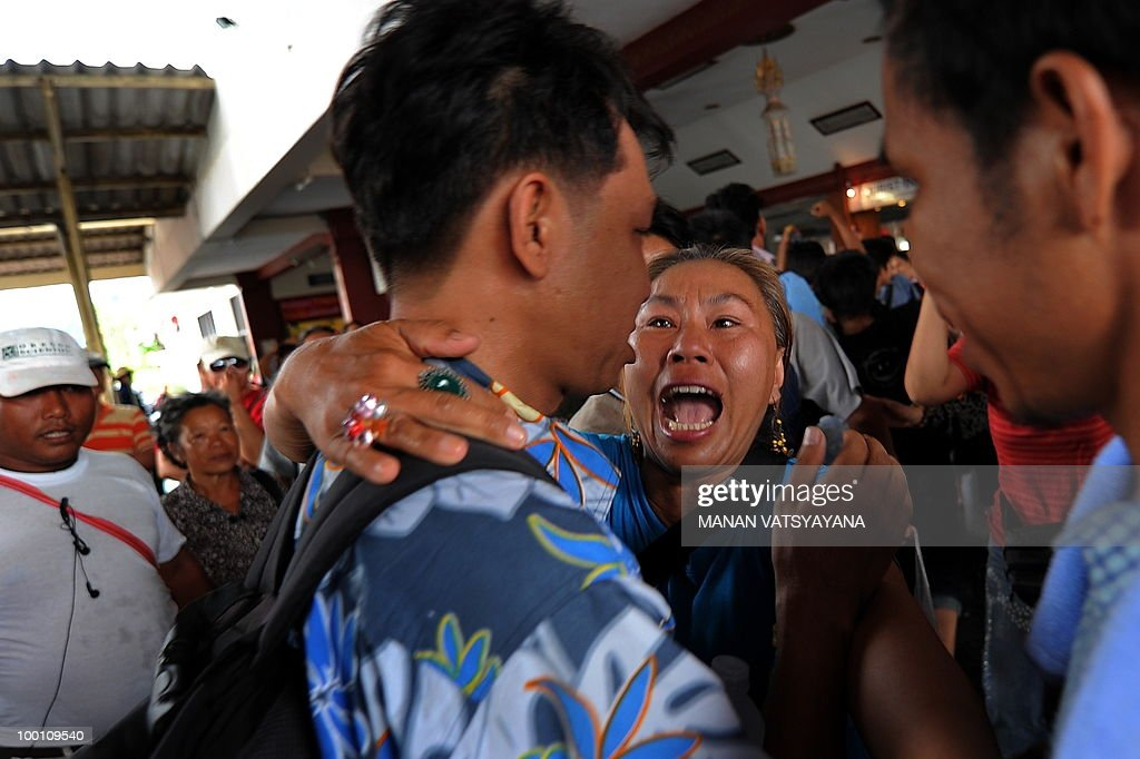 A Thai women embraces a Red Shirs anti-government protester as he arrives from Bangkok at the train station in Chiang Mai on May 21, 2010. Emotional 'Red Shirt' supporters gathered at a train station in northern Thailand, waving flags to welcome about 300 members of the movement dispersed from Bangkok.