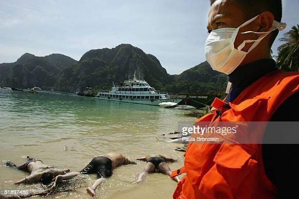 A Thai worker looks at dead bodies that washed up on the beach December 28 2004 in Phi Phi Village on Ton Sai Bay Thailand Hundreds were killed on...