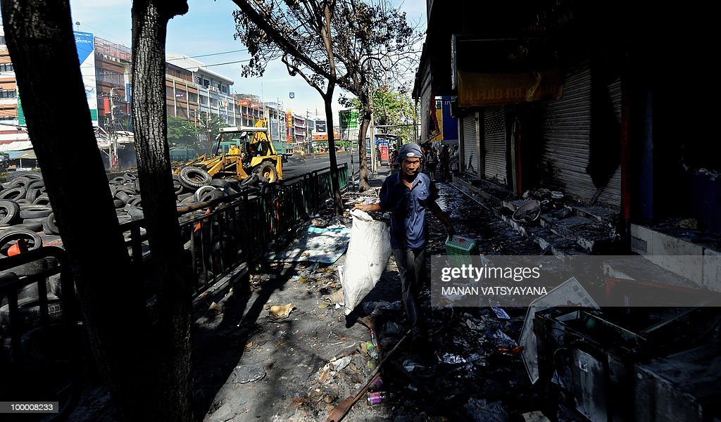 A Thai worker removes debris in front of damaged shops on Rama 4 road in Bangkok on May 20, 2010. The top Thai protest leader urged supporters of the anti-government 'Red Shirt' movement to refrain from violence after riots in the capital, saying 'democracy cannot be built on revenge.'