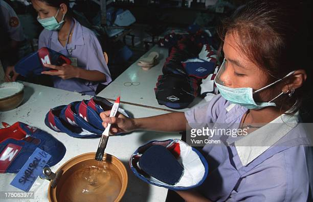 Thai worker uses a cloth face mask to protect herself from the the fumes from a pot of glue she is using to stick down shoe soles at a factory...
