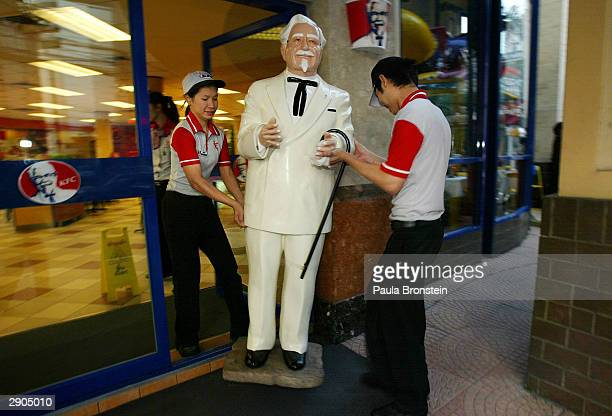 Thai workers carry a statue of Colonel Harland Sanders founder of Kentucky Fried Chicken out onto the street one of the fast food restaurants in...