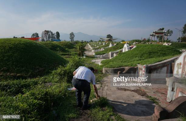 A ThaiChinese man picks up debris from a tomb ahead of Qingming Festival or Tomb Sweeping Day in a Chinese cemetery in Chonburi province on April 3...