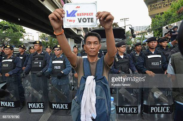 BANGKOK Thailand A supporter of former Thai Prime Minister Thaksin Shinawatra protests a military coup standing in front of police blocking a road in...