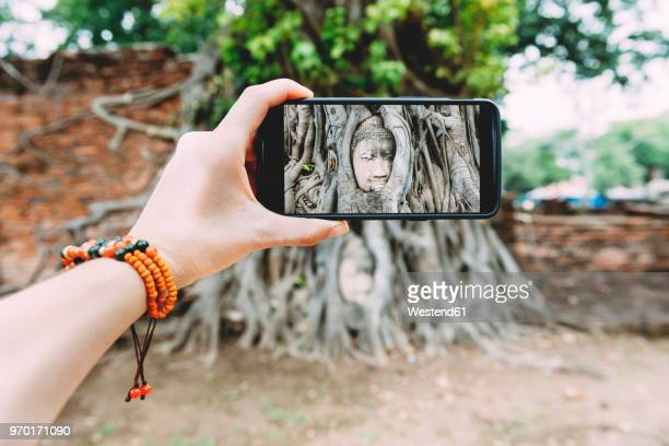 Thailand, Ayutthaya, Wat Mahathat, woman taking a picture with smartphone of buddha head in tree roots
