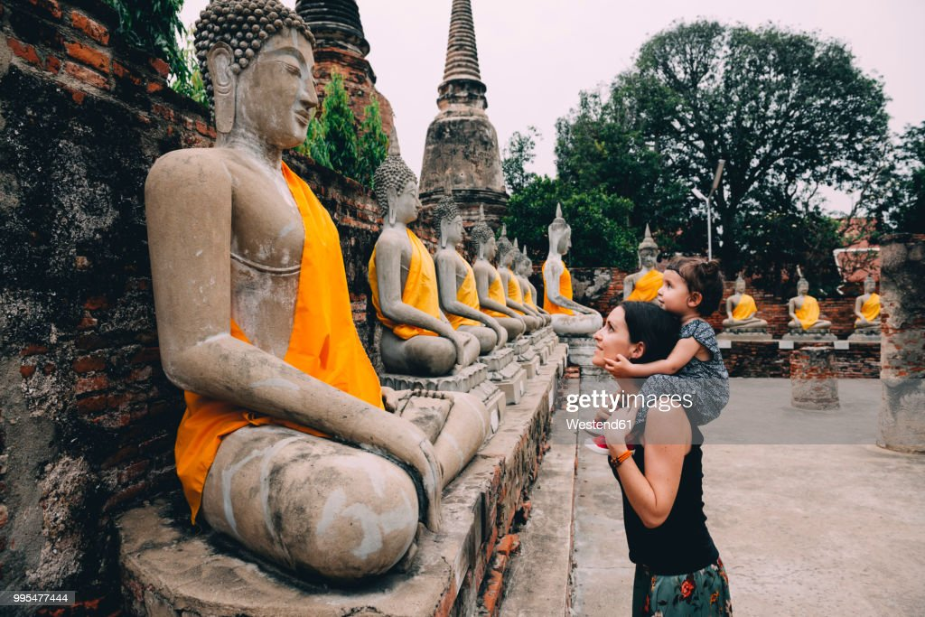 Thailand, Bangkok, Ayutthaya, Buddha statues in a row in Wat Yai Chai Mongkhon, mother and daughter in front of a buddha statue : Stock Photo