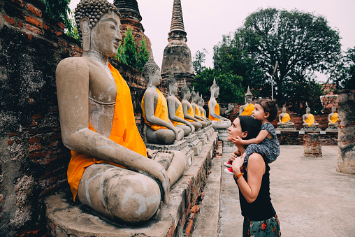 Thailand, Bangkok, Ayutthaya, Buddha statues in a row in Wat Yai Chai Mongkhon, mother and daughter in front of a buddha statue - gettyimageskorea