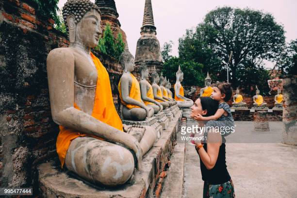 thailand, bangkok, ayutthaya, buddha statues in a row in wat yai chai mongkhon, mother and daughter in front of a buddha statue - travel destinations stock-fotos und bilder