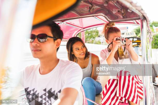 thailand, bangkok, friends riding tuk tuk taking pictures with an old camera - auto rickshaw stock pictures, royalty-free photos & images