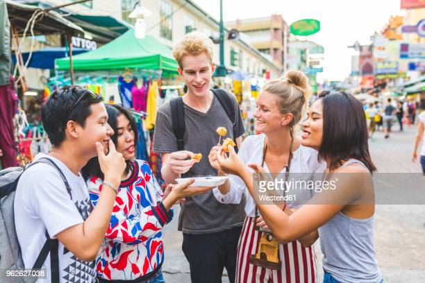 thailand, bangkok, khao san road, group of friends tasting local food on street market - street food stock pictures, royalty-free photos & images
