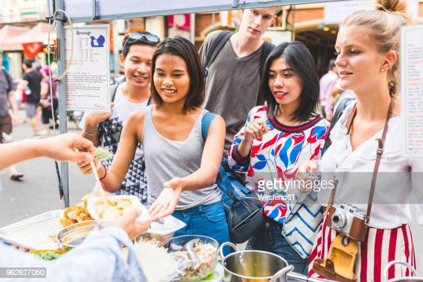 thailand, bangkok, khao san road, group of friends testing local food on street market - market stall stock pictures, royalty-free photos & images