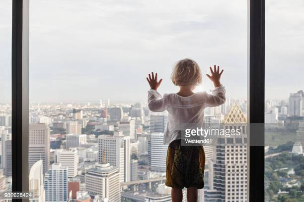 thailand, bangkok, little girl looking through window at cityscape - looking at view foto e immagini stock