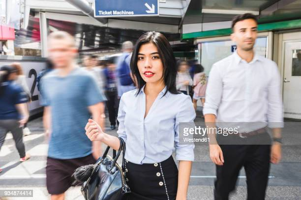 Thailand, Bangkok, portrait of businesswoman amidst moving people in the city