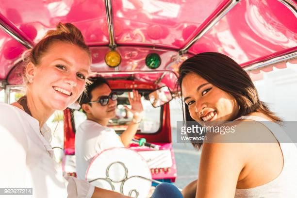 thailand, bangkok, portrait of smiling friends riding tuk tuk - magenta stock pictures, royalty-free photos & images