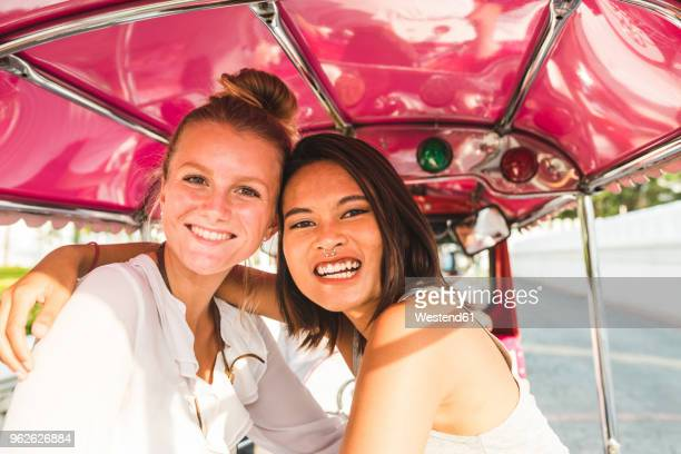 Thailand, Bangkok, portrait of two happy two friends riding tuk tuk