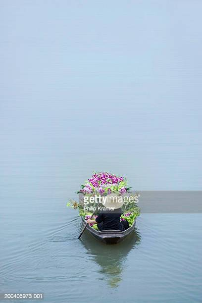 thailand, bangkok, vendor in boat filled with flowers, rear view - floating market stock pictures, royalty-free photos & images