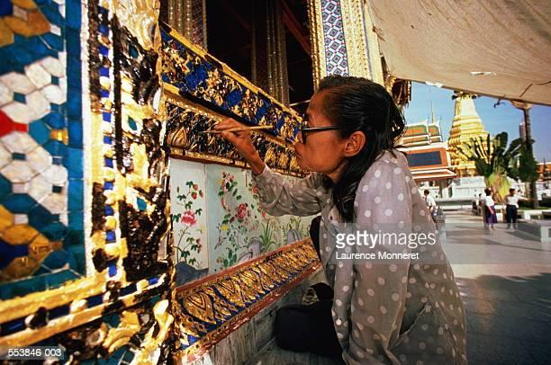 Thailand, Bangkok, woman restoring decoration on Wat Phra Keo Temple