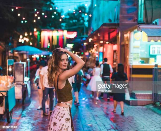 thailand, bangkok, young woman in the city on the street at night - escapade urbaine photos et images de collection
