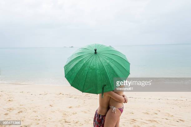 thailand, boy hugging his mother on the beach under a green umbrella - mother son shower stock photos and pictures