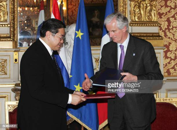 Thailand foreign minister Surakiart Sathirathai and his French counterpart Michel Barnier exchange documents after signing an agreement 25 May 2004...