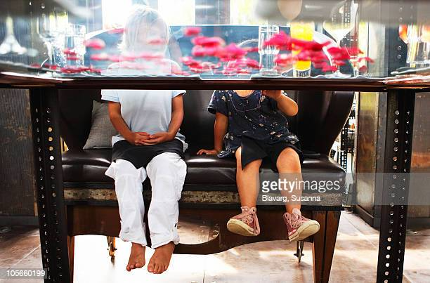 Thailand, girls sitting on sofa, view from under table