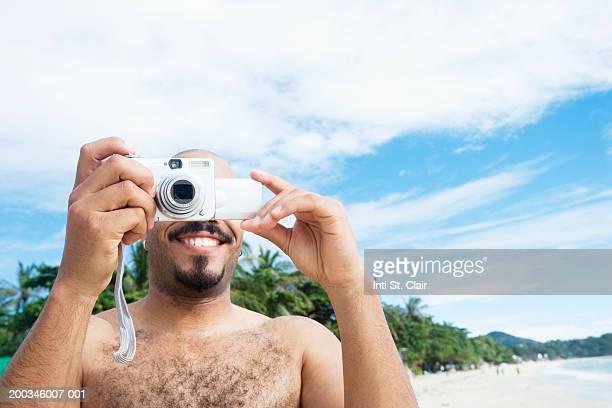 Thailand, Ko Samui, man taking digital photograph on beach, smiling