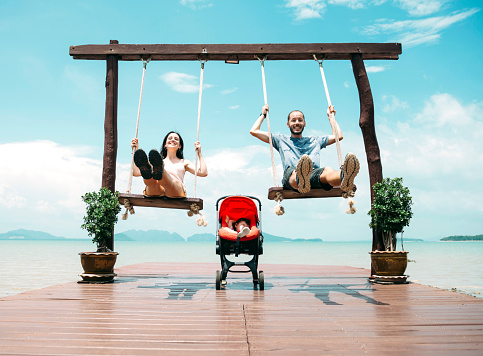 Thailand, Koh Lanta, happy parents on wooden swings in front of the sea and sleeping baby in a stroller - gettyimageskorea