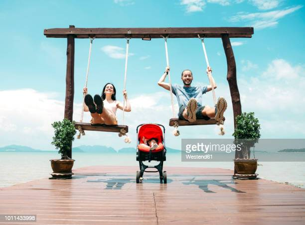 thailand, koh lanta, happy parents on wooden swings in front of the sea and sleeping baby in a stroller - ブランコ ストックフォトと画像