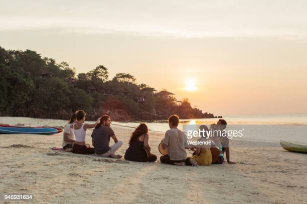thailand, koh phangan, group of people sitting on a beach with guitar at sunset - romantic sunset stock pictures, royalty-free photos & images