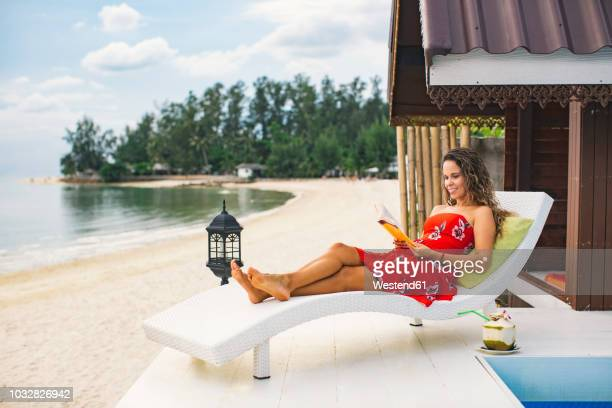 thailand, koh phangan, smiling woman reading book on terrace beside the beach - sun lounger stock pictures, royalty-free photos & images