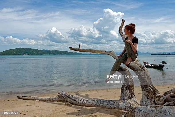 Thailand, Koh Samui, Teenage girl sitting on dead roots at Taling Ngam Beach