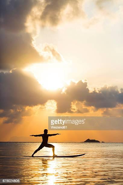 Thailand, man doing yoga on paddleboard at sunset, bridge position, warrior pose