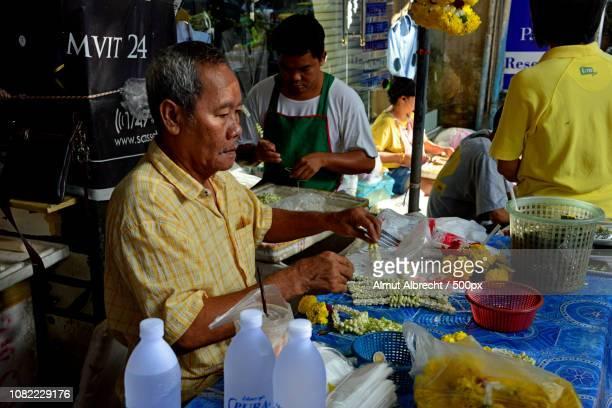 thailand man makes flowers for prayers