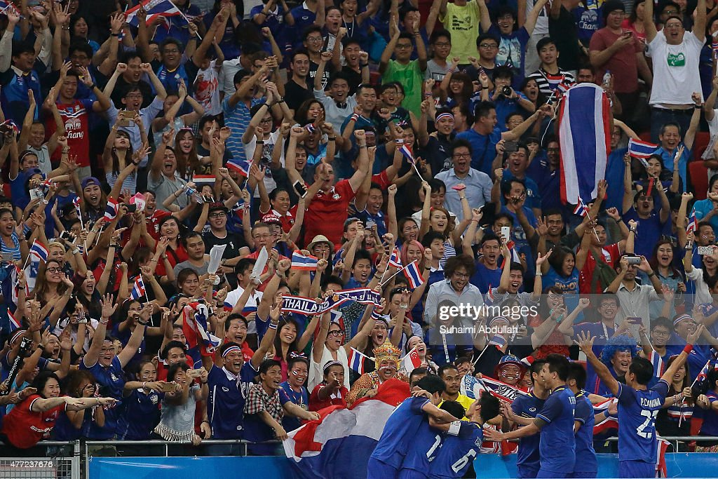 Thailand players (bottom) celebrate with fans after scoring a goal in the men's gold medal football match between Thailand and Myanmar at the National Stadium during the 2015 SEA Games on June 15, 2015 in Singapore.