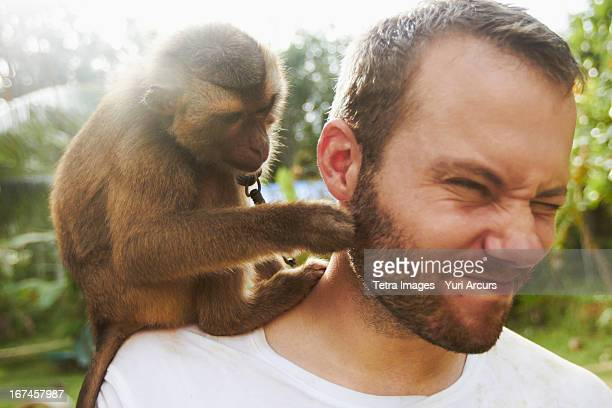 Thailand, Portrait of adult man with macaque monkey sitting on his shoulder