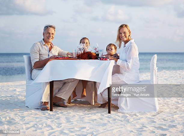 Thailand, Portrait of parents with daughters (8-9), (4-5) sitting at table on beach