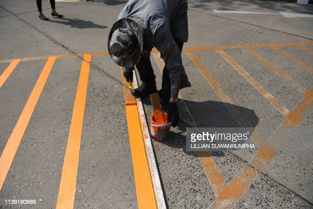 A Thailand Post Company Ltd employees repaints the roads outside their offices in honour of Thailand's King Maha Vajiralongkorn in Bangkok on April...