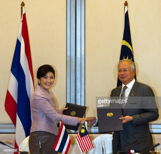 Thailand Prime Minister Yingluck Shinawatra exchanges documents with Malaysian Prime Minister Najib Razak after their meeting at the latter's office...