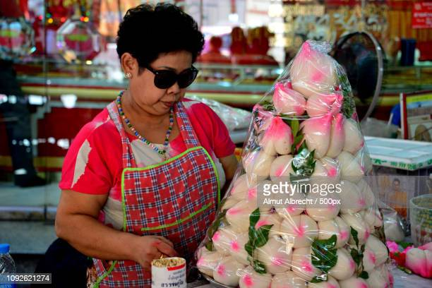 thailand woman decorates a pyramid of sweets
