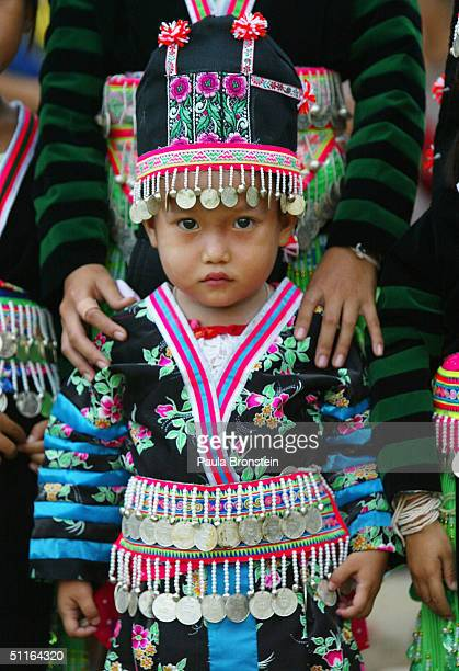 A Hmong child wearing traditional dress participates in a ceremony to honor the Queen of Thailand on her birthday August 12 2004 at Wat Tham Krabok...