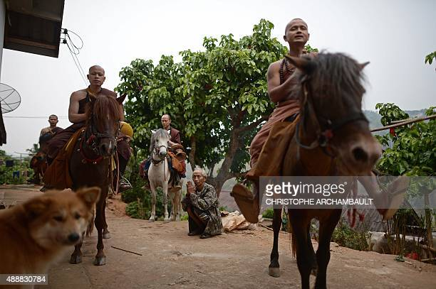ThailandreligiondrugssocialFEATURE by Marion THIBAUT This picture taken on April 8 2015 shows a resident praying after he offered alms to horseriding...