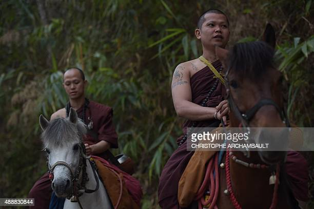 ThailandreligiondrugssocialFEATURE by Marion THIBAUT This picture taken on April 8 2015 shows Buddhist novice Ponsakorn Mayer and a monk riding...