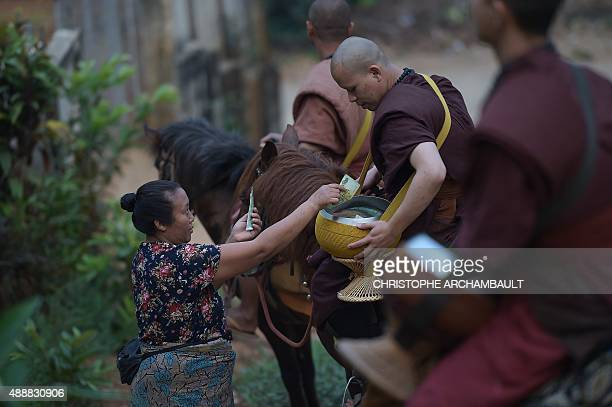 ThailandreligiondrugssocialFEATURE by Marion THIBAUT This picture taken on April 8 2015 shows a resident offering alms to monks riding horses during...