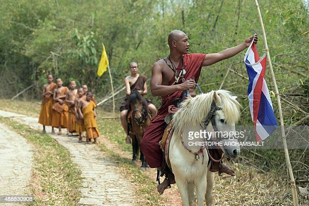 ThailandreligiondrugssocialFEATURE by Marion THIBAUT This picture taken on April 8 2015 shows a monk fixing a Thai flag to a pole as he leads...