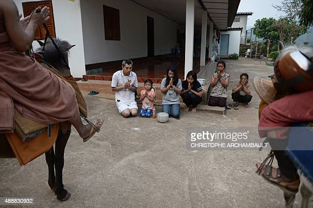 ThailandreligiondrugssocialFEATURE by Marion THIBAUT This picture taken on April 8 2015 shows residents praying after they offered alms to...