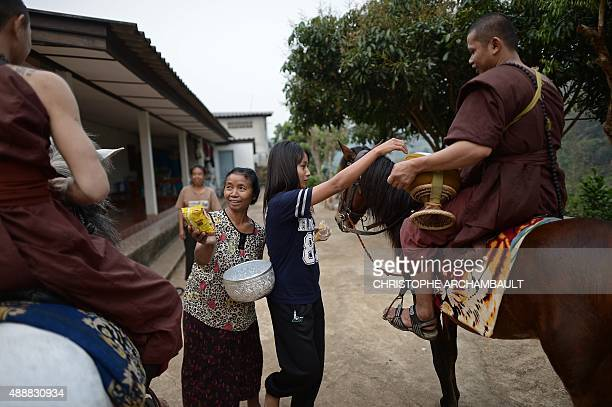 ThailandreligiondrugssocialFEATURE by Marion THIBAUT This picture taken on April 8 2015 shows residents offering alms to horseriding monks during...
